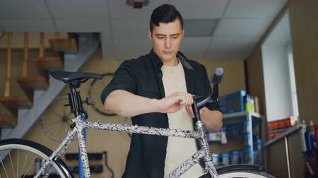 rukojeť : Strong handsome man skilled mechanic is concentrated on repairing handlebar of broken bicycle in his small workshop. Skilled people and maintenance concept. Dostupné videozáznamy