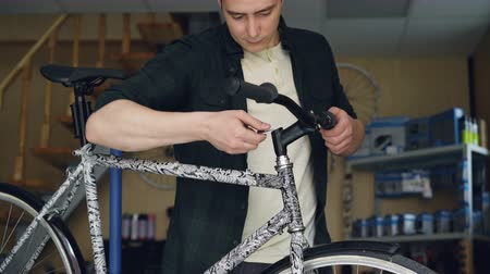 опытный : Tilt-up shot of young man bike repairman fixing broken handlebar of modern bicyle with tools. Repairing cycles, skilled people, busy workshop concept. Стоковые видеозаписи