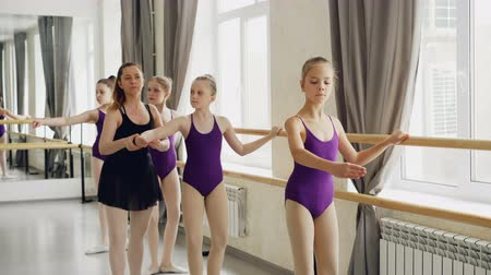 колготки : Diligent young ballet-dancers are doing plie and battement tendu while their female teacher is correcting wrong positions and giving instructions.
