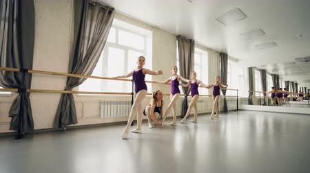 classical suit : Young students of ballet school are practising basic positions while their attentive female teacher is helping them to take correct postures and stretch legs.