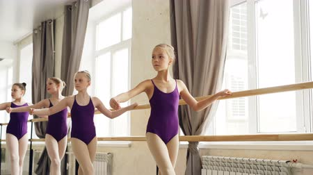 taniec towarzyski : Starting ballet-dancers are doing exercises at ballet barre in spacious ballroom, their teacher in leotard is helping them. Art, education and people concept.
