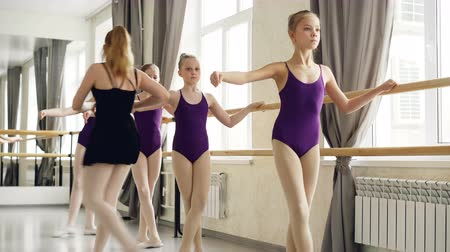 genç kız : Ballet teacher is helping her small female students with arms, hands and legs positions during lesson in dancing school. Girls are wearing trendy ballet suits and pointe-shoes. Stok Video
