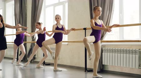 classical suit : Serious little girls are learning sequence of ballet positions at ballet class with helpful teacher. Spacious light dancing hall with large windows and ballet barre is visible.