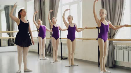 classical suit : Diligent girls are learning forward and backward bends and arm movements during ballet lesson with strict teacher. Students wearing beautiful bodysuits are holding ballet barre. Stock Footage