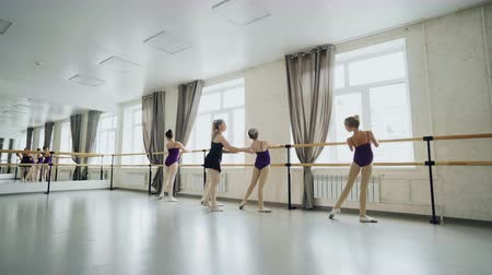 строгий : Slim girls are learning backward bends practising ballet movements in spacious light studio with large windows and ballet bar. Helpful tutor is teaching them.