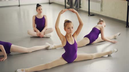esneme : Flexible children ballet dancers doing stretching exercises on studio floor practising leg-split, backward and forward bends and arms movement.