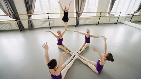classical suit : High angle view of diligent little ballet dancers practising forward bends sitting on floor in studio stretching and moving arms under guidance of ballet teacher. Stock Footage