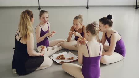 ballroom : Little female gymnasts are eating pizza sitting on floor with their teacher after training, talking and laughing. Communication, childhood and dancing school concept. Stock Footage