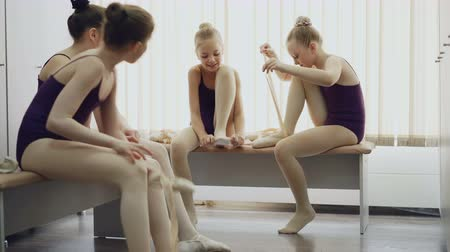 dressing : Cheerful kids ballet dancers putting on pointe-shoes and talking sitting on benches in light changing room. Footwear, children and communication concept.