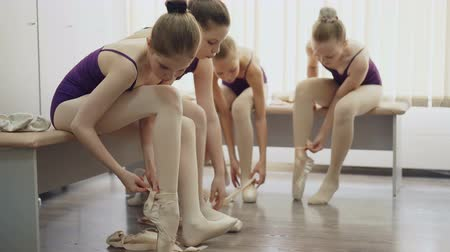 тапки : Slim girls ballet students are putting on ballet-shoes and talking sitting on benches in light locker room. Footwear, children and communication concept.