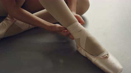 tancerka : Close-up shot of girls feet in ballet slippers and hands trying to put on footwear and tie ribbon around leg beautifully. Pointe-shoes, dancing and attire concept.