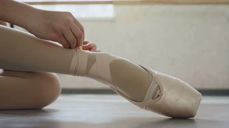 тапочка : Close-up shot of little girls foot in pointe shoe and hands putting on professional footwear and tying ribbon around leg. Ballet-shoes, dancing and attire concept. Стоковые видеозаписи