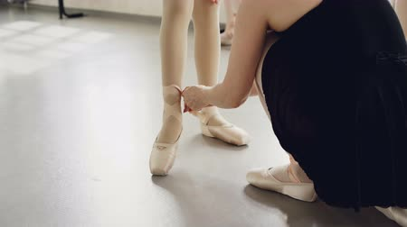 özel öğretmen : Helpful teacher is putting pointe-shoes on little students feet tying ribbons around small legs before ballet lesson. Choreography, footwear and people concept.