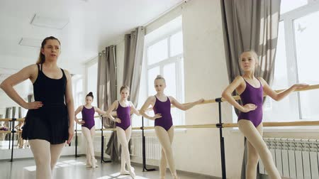 rehberlik : Strict ballet teacher is demonstrating legs and arms positions while diligent little girls are repeating after her holding ballet bar and looking at tutor.