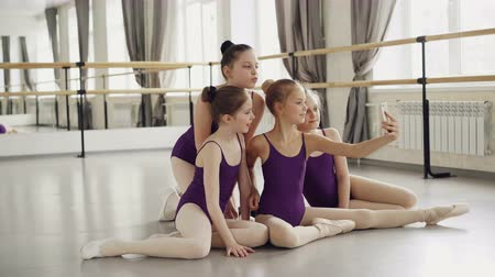 dinlenmek : Young ballet students in bodysuits are taking selfie with smartphone and posing looking at camera and sitting on dance floor during break between ballet classes.