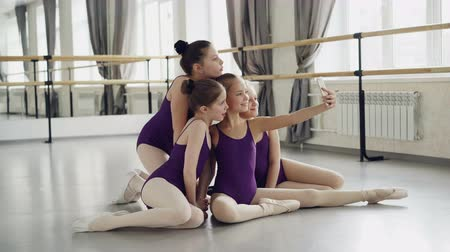 taniec towarzyski : Cheerful children girls in leotards are taking selfie with smartphone and posing looking at camera while sitting on dancehall floor during break in ballet school. Wideo
