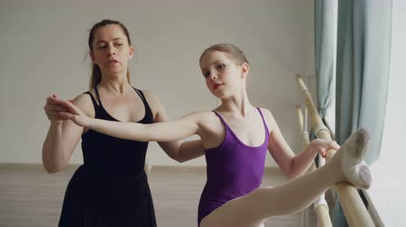 özel öğretmen : Ballet teacher professional ballerina is teaching girl arm movements and bends at ballet barre during individual lesson in dancing school. Education and people concept.