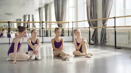 classical suit : Ballet teacher experienced ballerina is dancing on tiptoes demonstrating movements to her little students sitting on floor, watching tutor then clapping hands. Stock Footage