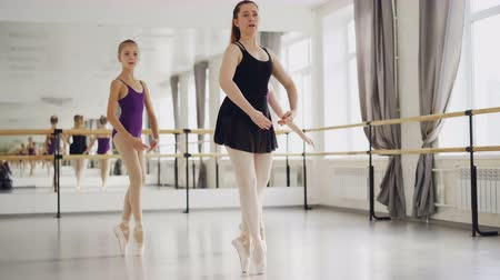 profesyonel meslek : Two girls ballet dancers are practising dancing on tiptoes with their experienced teacher during ballet lesson in studio. Large mirror, ballet barre and windows are visible. Stok Video