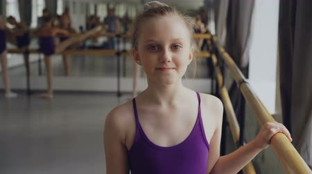 shy girl : Portrait of beautiful little girl starting ballet-dancer looking at camera and smiling standing in ballet class in spacious light dancehall. Art and childhood concept. Stock Footage