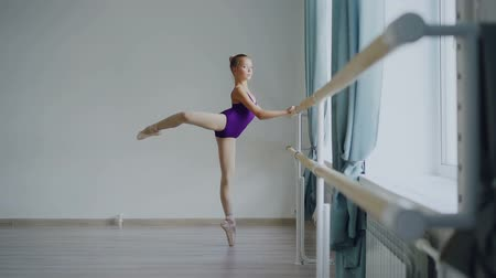 taniec towarzyski : Slow motion of little ballet-dancer standing on tiptoes and raising leg backward practising alone at ballet barre in light ballroom in art studio.