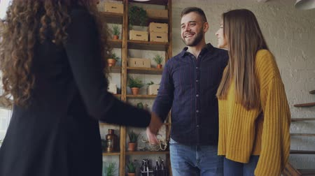 застежка : Happy young couple is buying new house shaking hands with female agent then hugging and laughing. Relocation, happiness and accommodation concept. Стоковые видеозаписи