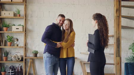 застежка : Friendly agent is giving keys to young couple buyers of new house, happy spouses are hugging and kissing, man is shaking hands with broker making deal.