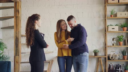 toka : Real estate buyers are getting keys from housing agent after successful deal, kissing and hugging with happiness and shaking hands to female broker. Stok Video