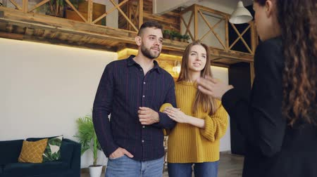 deslocalização : Confident housing agent is showing spacious modern house with beautiful interior to happy young couple, people are smiling and talking looking around.