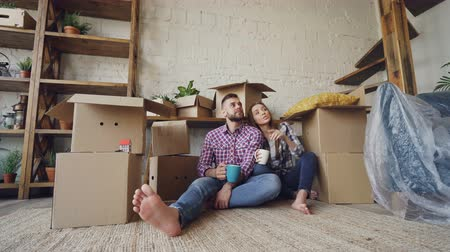 nowe mieszkanie : Adorable couple is talking, kissing and holding mugs while sitting on floor of new flat after relocation. Numerous boxes, packed furniture and plants are visible.