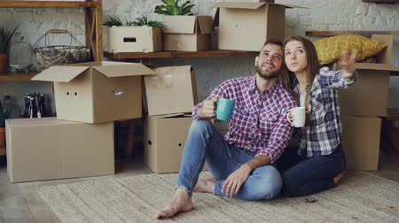 nowe mieszkanie : Girlfriend and boyfriend are talking making plans sitting on floor of new purchased apartment, looking around and holding mugs. Relationship and relocation concept. Wideo
