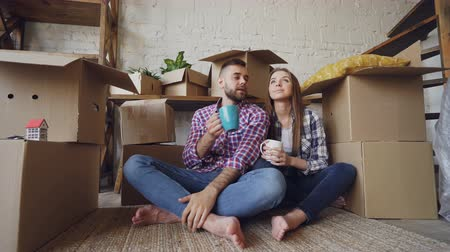 dama : Young husband and wife are talking, looking around and kissing sitting on floor after moving to new house. Nice interior and many boxes with personal things are visible.