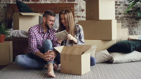 nowe mieszkanie : Married couple is unpacking personal things while sitting on floor in new house. Young people are talking and laughing, carton boxes and double bed are visible.