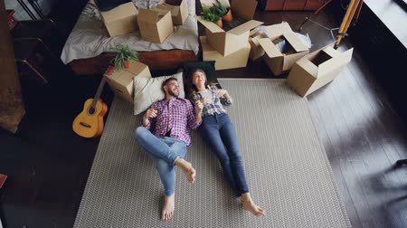 dywan : High shot of young couple lying on floor of their new house in bedroom, talking, laughing and holding hands. Carton boxes, guitar, carpet and bed are visible. Wideo