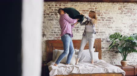 almofada : Joyful young couple is having pillow fight, having fun and laughing then hugging and kissing on double bed. Modern lifestyle and relationship concept.
