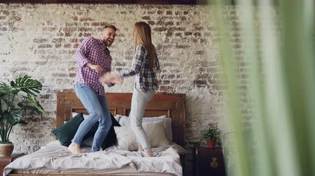 carelessness : Cheerful young lovers are dancing on bed having fun in bedroom at home and laughing carelessly. Happy people, modern lifestyle and relationship concept.