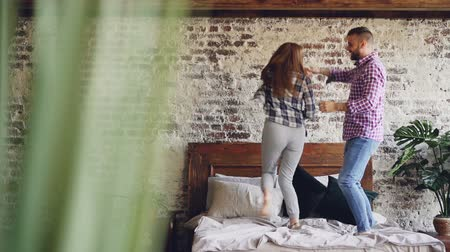 carelessness : Slow motion of happy young lovers dancing on double bed having fun in bedroom and laughing carelessly. Cheerful people, modern lifestyle and relationship concept.