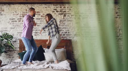 buta : Slow motion of happy young lovers dancing on double bed having fun in bedroom and laughing carelessly. Cheerful people, modern lifestyle and relationship concept.