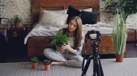 vlogging : Young smiling blogger in casual clothing is holding flowers, talking and recording video blog for online vlog about house plants using camera on tripod.