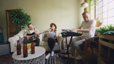 rehearsing : Pretty vocalist is singing looking at paper with lyrics while her friends are playing musical instruments keyboard and guitar during rehearsal in home studio.