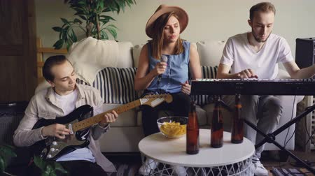 певец : Vocalist pretty blonde is singing and snapping fingers while her friends and colleagues from musical band are playing the keyboard and the electric guitar.