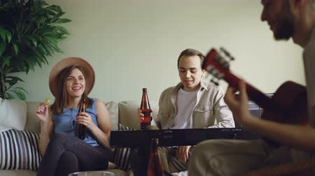 kytarista : Musical band is having break during rehearsal, young people are talking, eating snacks and drinking beer. Bearded guy is playing the guitar, others are singing and laughing.