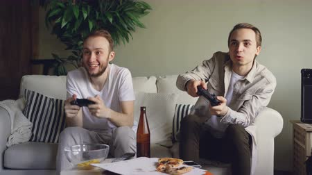premente : Careless students playing video game watching screen and pressing joystick buttons, one is losing one is winning and happy. Friendship and technology concept.