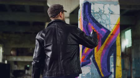 vandalismo : Rear view of male graffiti artist in leather jacket painting on damaged column inside empty industrial building. Young people, creativity, casual clothing and modern art concept.