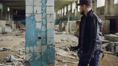 vandalismo : Graffiti artist bearded guy is painting on pillar in abandoned building with bright aerosol paint spray. Pan shot of empty industrial building with dirty walls and broken windows. Stock Footage
