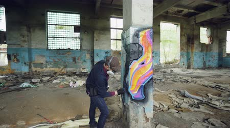 vandalismo : Pan shot of adult man graffiti artist in protective face mask and gloves painting on high pillar inside damaged empty industrial building. Creativity and people concept. Stock Footage