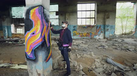 vandalismo : Young man professional graffiti painter is working inside abandoned building, he is painting with spray aerosol paint on high column. Modern art and creativity concept.