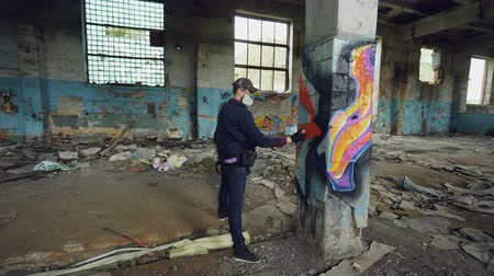 vandalismo : Male graffiti artist is decorating old damaged column inside empty industrial building with abstract pictures. Modern painter is using aerosol spray paint.
