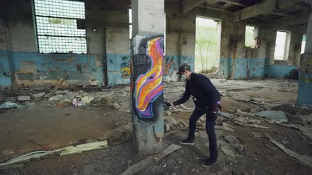 vandalismo : Graffiti painter is protective mask and gloves is drawing on old column in dirty empty building using aerosol paint. Young man is wearing casual clothes and cap. Stock Footage