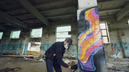 vandalismo : Urban street artist is painting graffiti in abandoned building with dirty walls and windows, he is using paint spray. Modern artwork and creative people concept. Stock Footage